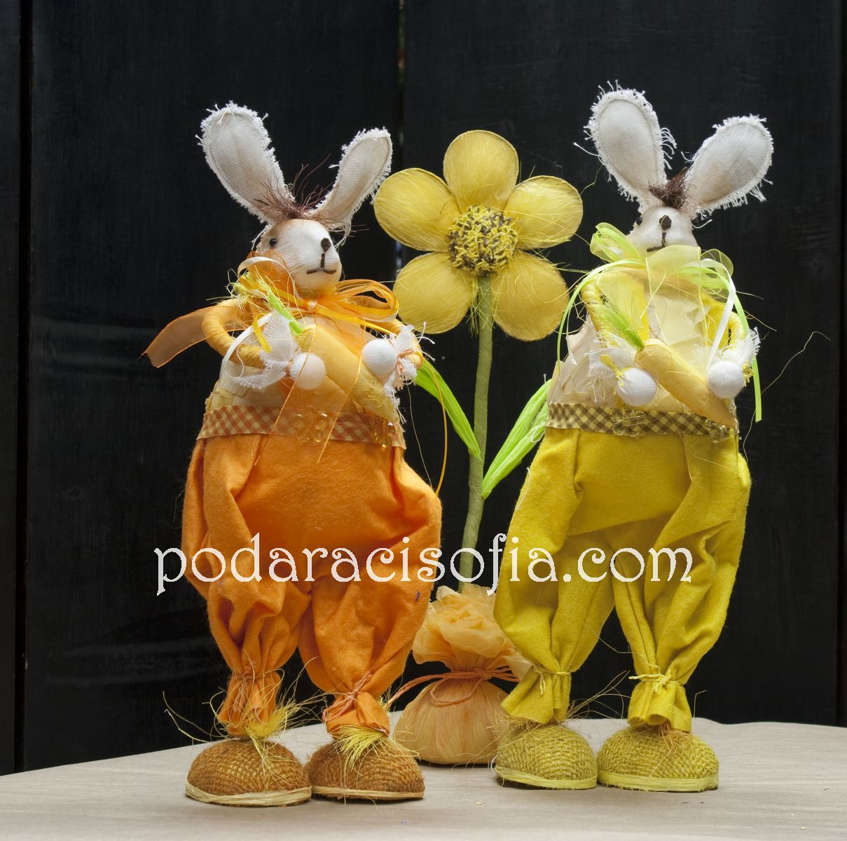 Високи великденски зайци облечени в оранжеви и жълти дрехи от магазин за подаръци Gifts