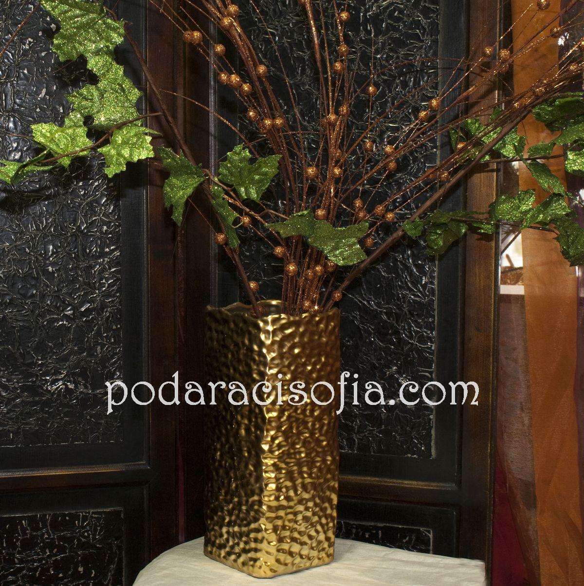 Вазата в златно е пищна и тържествена. Богатата украса в същия стил придава празничност.